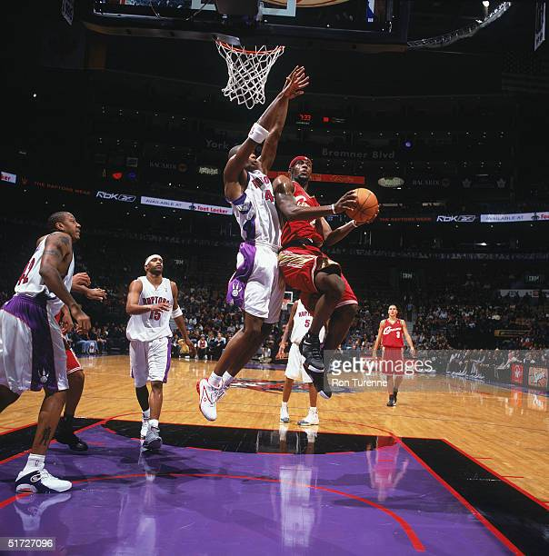 LeBron James of the Cleveland Cavaliers shoots past Chris Bosh of the Toronto Raptors during the game at the Air Canada Centre in Toronto Canada on...
