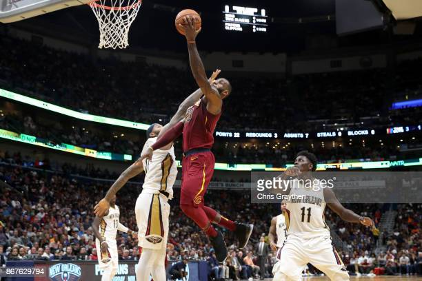 LeBron James of the Cleveland Cavaliers shoots the ball over DeMarcus Cousins of the New Orleans Pelicans at the Smoothie King Center on October 28...