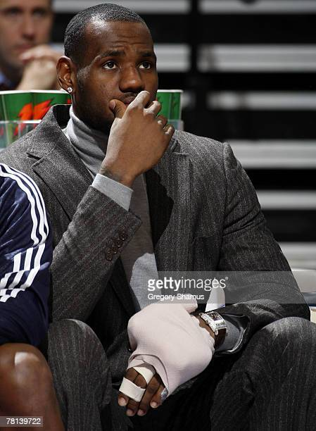 LeBron James of the Cleveland Cavaliers sits on the bench in street clothes after hurting his hand against the Detroit Pistons on November 28 2007 at...