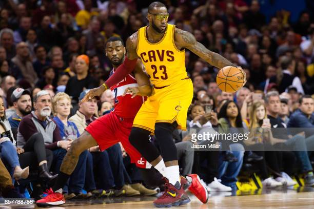 LeBron James of the Cleveland Cavaliers spins away from John Wall of the Washington Wizards during the first half at Quicken Loans Arena on March 25...