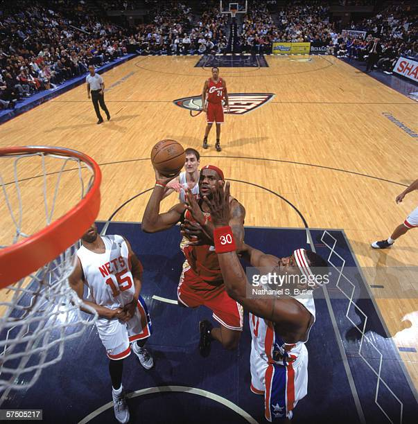LeBron James of the Cleveland Cavaliers takes a shot against Clifford Robinson of the New Jersey Nets at Continental Airlines Arena in East...