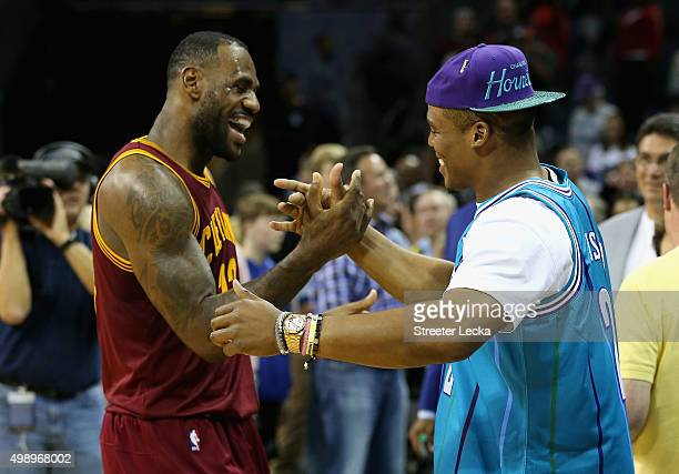 LeBron James of the Cleveland Cavaliers talks to Cam Newton quarterback of the Carolina Panthers after the Cavaliers defeated the Hornets 9590 at...