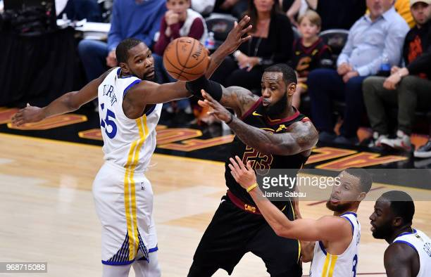 LeBron James of the Cleveland Cavaliers throws a pass around Stephen Curry and Kevin Durant of the Golden State Warriors in the first half during...