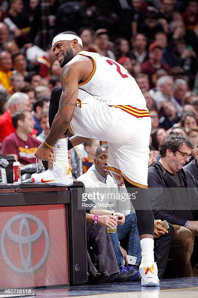 LeBron James of the Cleveland Cavaliers ties his shoe laces against the Sacramento Kings on January 30 2015 at Quicken Loans Arena in Cleveland Ohio...