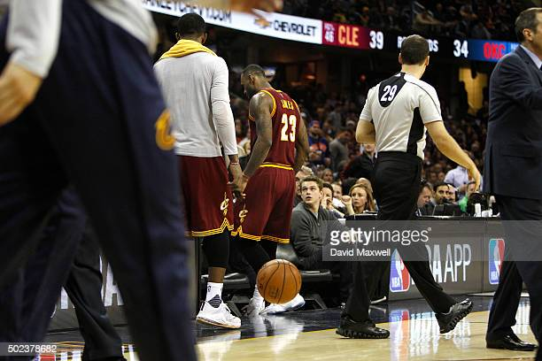 LeBron James of the Cleveland Cavaliers walks courtside during a timeout to check on Ellie Day wife of professional golfer Jason Day after he crashed...