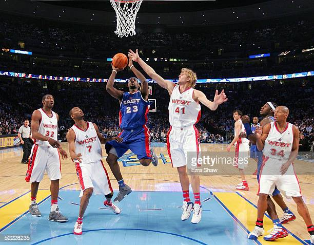 LeBron James of the Eastern Conference All-Stars goes up for a shot over Rashard Lewis and Dirk Nowitzki of the Western Conference All-Stars during...
