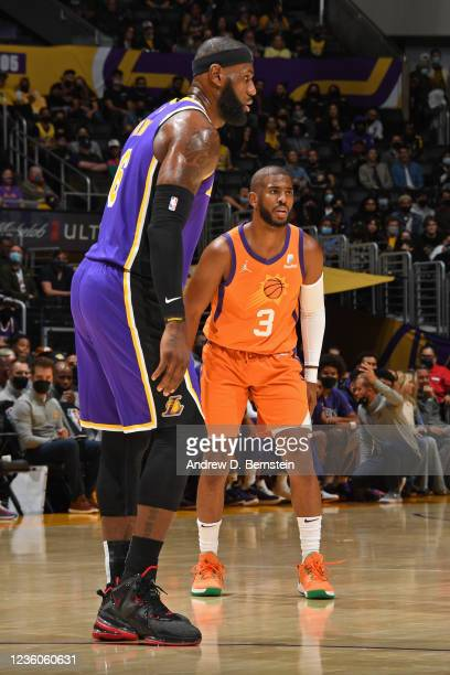 LeBron James of the Los Angeles Lakers and Chris Paul of the Phoenix Suns stand on the court on October 22, 2021 at STAPLES Center in Los Angeles,...