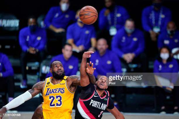 LeBron James of the Los Angeles Lakers and CJ McCollum of the Portland Trail Blazers battle for possession during the second half in Game 1 of Round...