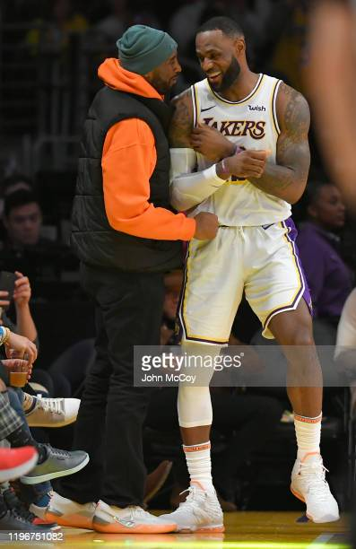 LeBron James of the Los Angeles Lakers and Kobe Bryant have a moment on the sideline during a game against the Dallas Mavericks at Staples Center on...