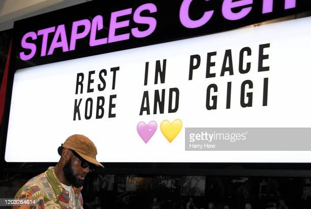 LeBron James of the Los Angeles Lakers arrives for the game against the Portland Trail Blazers as he passes a sign to honor Kobe and Gigi Bryant at...