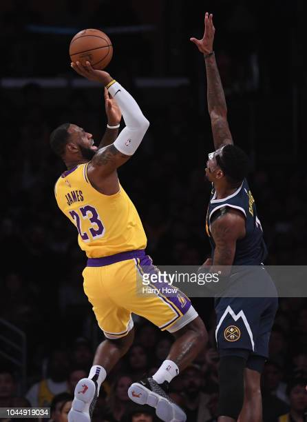 LeBron James of the Los Angeles Lakers attempts a shot in front of Torrey Craig of the Denver Nuggets during a preseason game at Staples Center on...