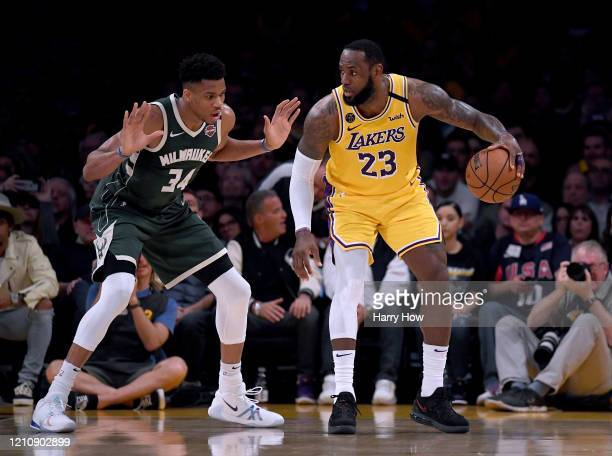 LeBron James of the Los Angeles Lakers backs in on Giannis Antetokounmpo of the Milwaukee Bucks during the third quarter at Staples Center on March...