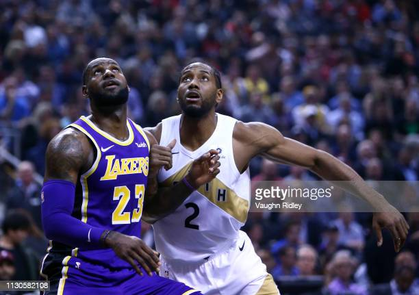 LeBron James of the Los Angeles Lakers battles for space with Kawhi Leonard of the Toronto Raptors during the first half of an NBA game at Scotiabank...
