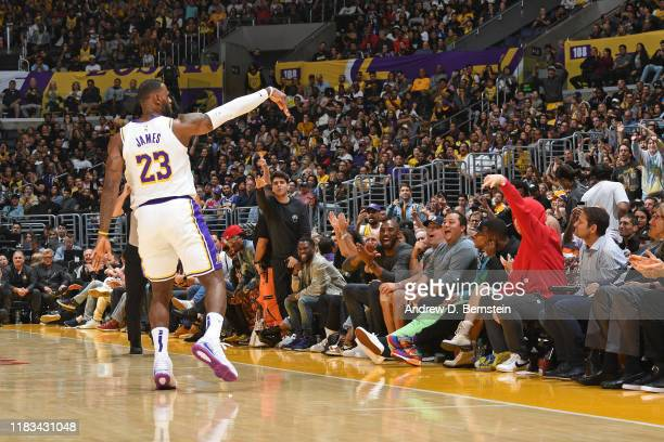LeBron James of the Los Angeles Lakers celebrates a three point basket with the fans and Kobe Bryant during the game against the Atlanta Hawks on...