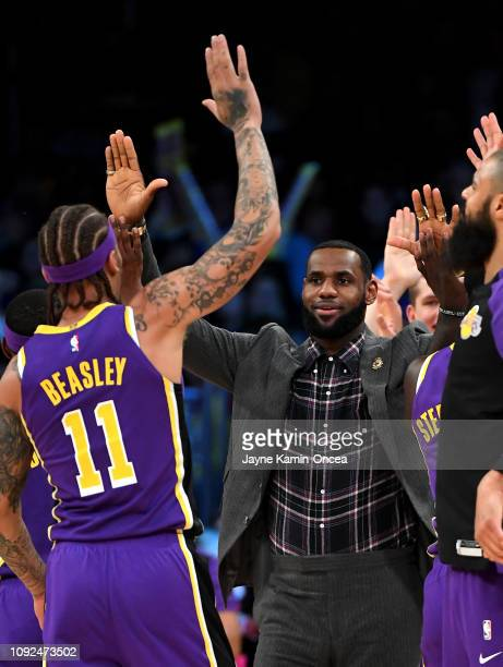 LeBron James of the Los Angeles Lakers celebrates from the bench with Michael Beasley of the Los Angeles Lakers during the game against the Detroit...