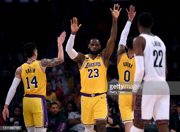 LeBron James of the Los Angeles Lakers celebrates his basket and a Brooklyn Nets foul with Danny Green and Kyle Kuzma during the first half at...