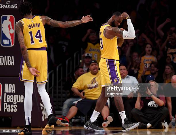 LeBron James of the Los Angeles Lakers celebrates his dunk in front of Brandon Ingram during a preseason game against the Denver Nuggets at Staples...