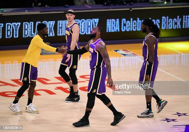LeBron James of the Los Angeles Lakers celebrates the end of the first half with Dennis Schroder as Alex Caruso and Montrezl Harrell of the Los...