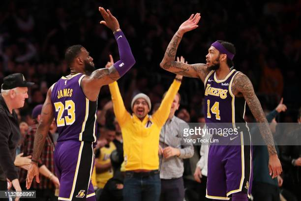 LeBron James of the Los Angeles Lakers celebrates with Brandon Ingram after making a threepointer against Jrue Holiday of the New Orleans Pelicans...