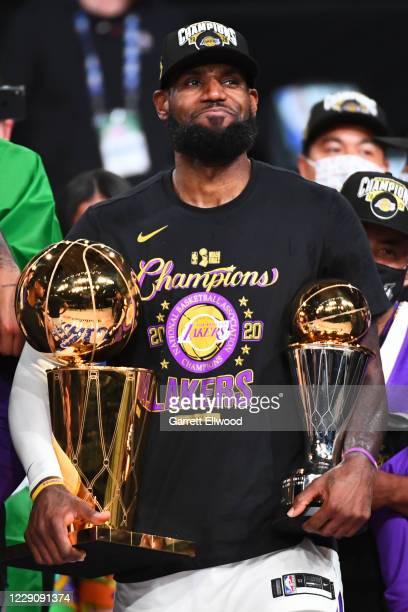 LeBron James of the Los Angeles Lakers celebrates with the Larry O'Brien Finals Trophy and Bill Russell Finals MVP Trophy after Game Six of the NBA...