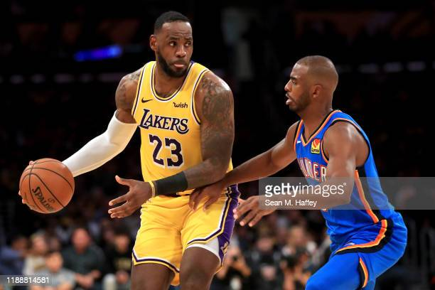 LeBron James of the Los Angeles Lakers controls the ball against Chris Paul of the Oklahoma City Thunder during the second half of a game at Staples...
