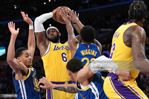 LeBron James of the Los Angeles Lakers controls the ball against Andrew Wiggins and Jordan Poole of the Golden State Warriors during the second half...