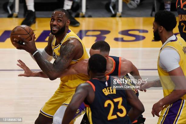 LeBron James of the Los Angeles Lakers controls the ball as Draymond Green and Stephen Curry of the Golden State Warriors defend during the first...