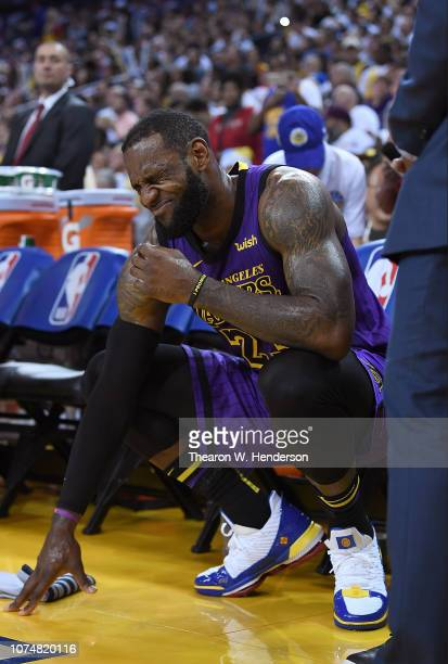 LeBron James of the Los Angeles Lakers crouches down in pain on the bench after he was hurt against the Golden State Warriors during the second half...