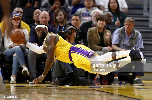 LeBron James of the Los Angeles Lakers dives for the ball during their game against the Golden State Warriors at Chase Center on October 05 2019 in...
