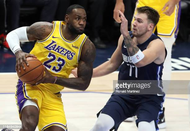 LeBron James of the Los Angeles Lakers dribbles the ball against Luka Doncic of the Dallas Mavericks in the first quarter at American Airlines Center...