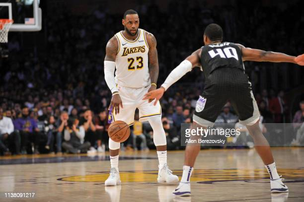 LeBron James of the Los Angeles Lakers dribbles the ball while being defended by Harrison Barnes of the Sacramento Kings at Staples Center on March...