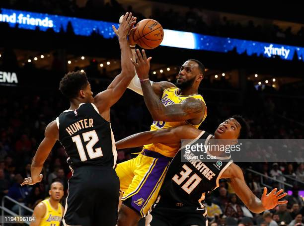 LeBron James of the Los Angeles Lakers drives against De'Andre Hunter and Damian Jones of the Atlanta Hawks in the first half at State Farm Arena on...