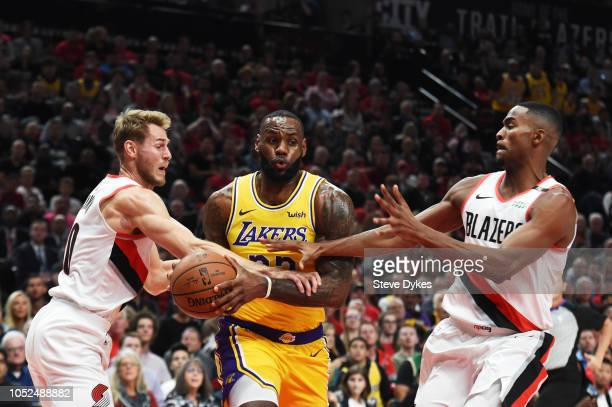 LeBron James of the Los Angeles Lakers drives against Jake Layman and Maurice Harkless of the Portland Trail Blazers in the first quarter of their...