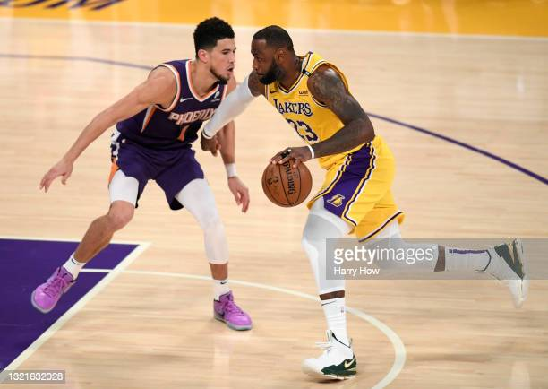 LeBron James of the Los Angeles Lakers drives on Devin Booker of the Phoenix Suns in the fourth quarter during game six of the Western Conference...