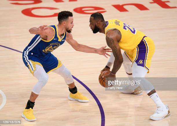 LeBron James of the Los Angeles Lakers drives on Stephen Curry of the Golden State Warriors during the first half at Staples Center on January 18,...