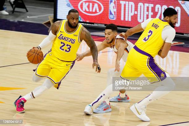 LeBron James of the Los Angeles Lakers drives the ball as Anthony Davis sets a pick on Devin Booker of the Phoenix Suns during the first half of the...