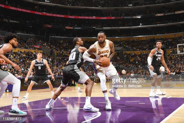 LeBron James of the Los Angeles Lakers drives through the paint during the game against Harrison Barnes of the Sacramento Kings on March 24 2019 at...