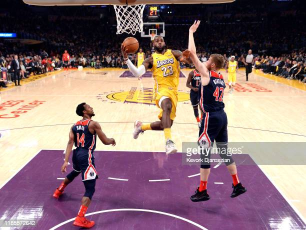 LeBron James of the Los Angeles Lakers drives to the basket against Davis Bertans and Ish Smith of the Washington Wizards during the first half at...