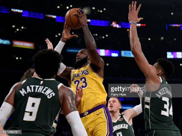 LeBron James of the Los Angeles Lakers drives to the basket between Giannis Antetokounmpo and Wesley Matthews of the Milwaukee Bucks during the first...