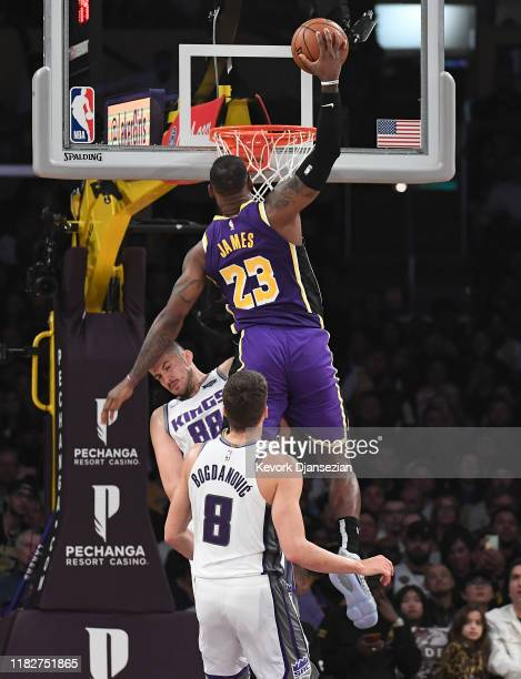 LeBron James of the Los Angeles Lakers dunks over Nemanja Bjelica of the Sacramento Kings during the first half at Staples Center on November 15 2019...