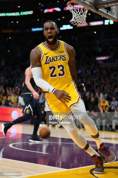 LeBron James of the Los Angeles Lakers dunks the basketball against Paul Millsap of the Denver Nuggets on October 25 2018 at STAPLES Center in Los...