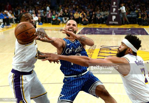 LeBron James of the Los Angeles Lakers fouls Evan Fournier of the Orlando Magic as he drives to the basket against JaVale McGee during the first half...