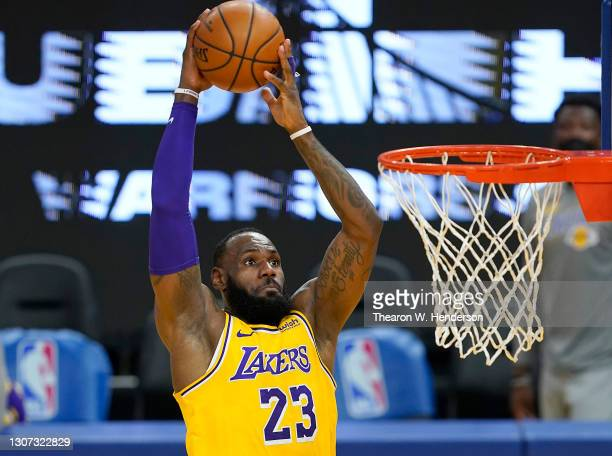 LeBron James of the Los Angeles Lakers goes up for a slam dunk against the Golden State Warriors during the first half of an NBA basketball game at...