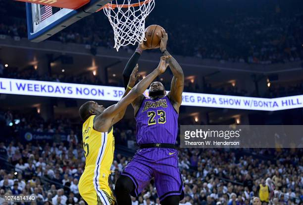 LeBron James of the Los Angeles Lakers goes up to shoot and get fouled by Kevin Durant of the Golden State Warriors during the first half of their...