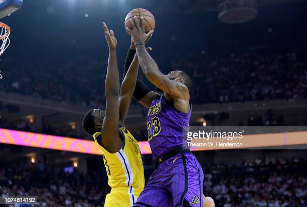 LeBron James of the Los Angeles Lakers goes up to shoot and gets fouled by Draymond Green of the Golden State Warriors during the first half of their...