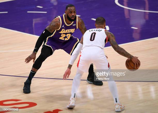 LeBron James of the Los Angeles Lakers guards Damian Lillard of the Portland Trail Blazers during the second quarter at Staples Center on February...
