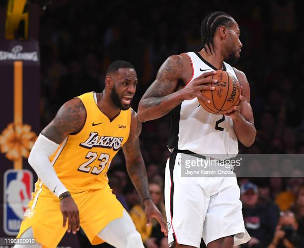 LeBron James of the Los Angeles Lakers guards Kawhi Leonard of the Los Angeles Clippers in the game at Staples Center on December 25 2019 in Los...