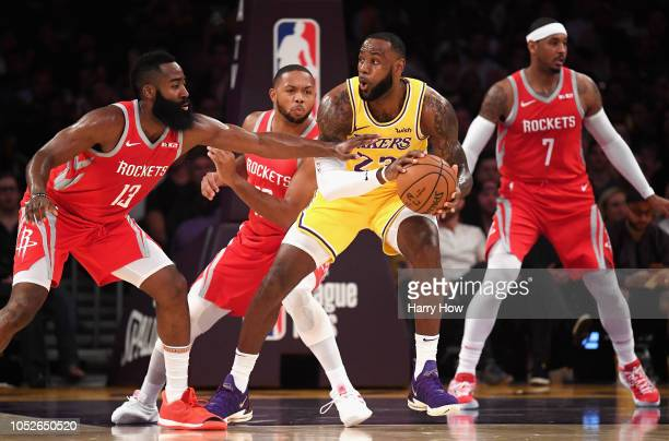 LeBron James of the Los Angeles Lakers handles the ball against James Harden Eric Gordon and Carmelo Anthony of the Houston Rockets during the first...