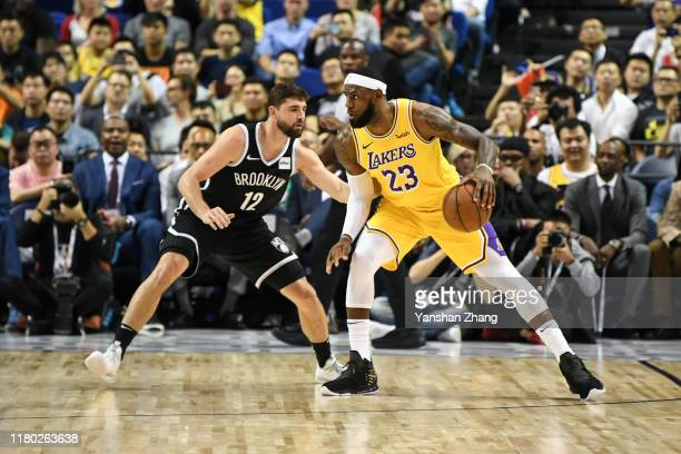 LeBron James of the Los Angeles Lakers handles the ball against Joe Harris of the Brooklyn Nets during a preseason game as part of 2019 NBA Global...