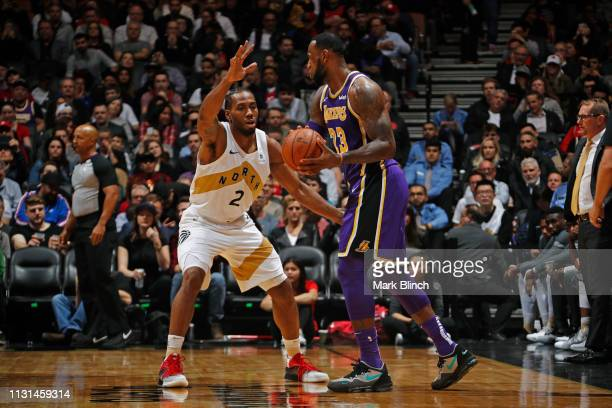 LeBron James of the Los Angeles Lakers handles the ball against Kawhi Leonard of the Toronto Raptors on March 14 2019 at the Scotiabank Arena in...